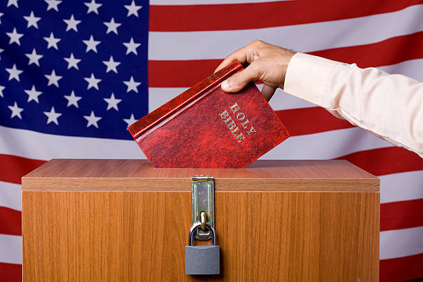 human hand inserting bible to ballot box before american flag - 大比大 聖經人物 個照片及圖片檔