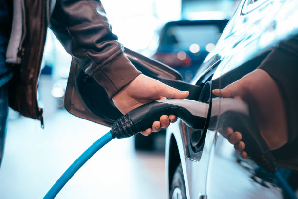 Human hand is holding Electric Car Charging connect to Electric car stock photo