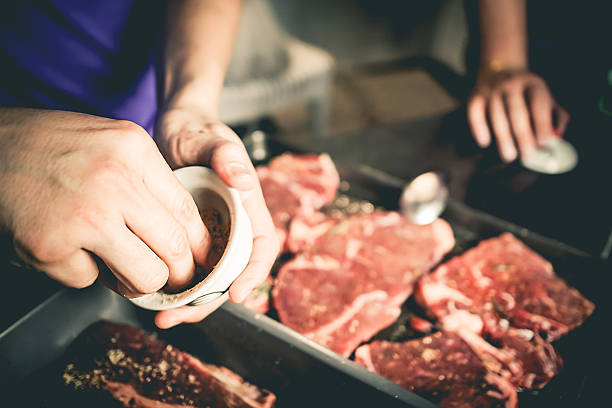 Human hand is preparing BBQ steak for party. stock photo