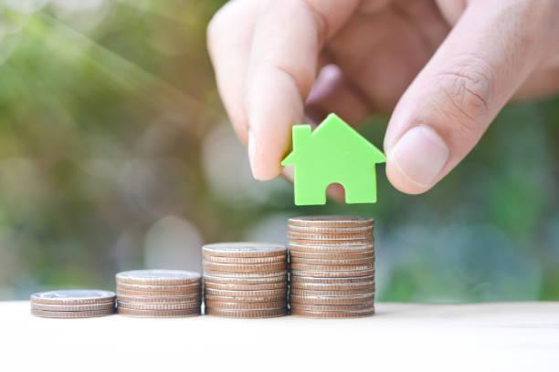 menschliche hand home modell gesetzt wachsenden münze stack für geld sparen für haus kauf von fonds-konzept - mieterhöhung stock-fotos und bilder