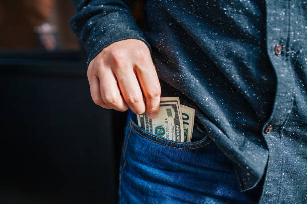 human hand is putting money in the pocket - pocket stock photos and pictures