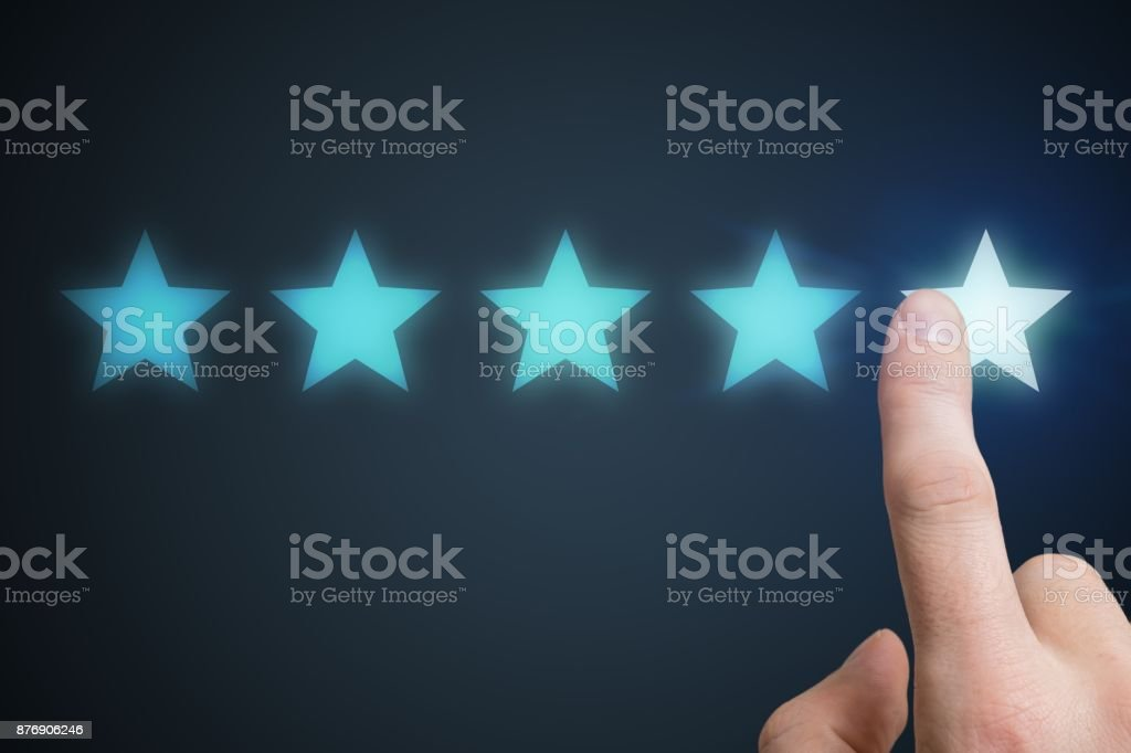 Human hand is rating with 5 stars. Ranking and customer satisfaction concept. stock photo