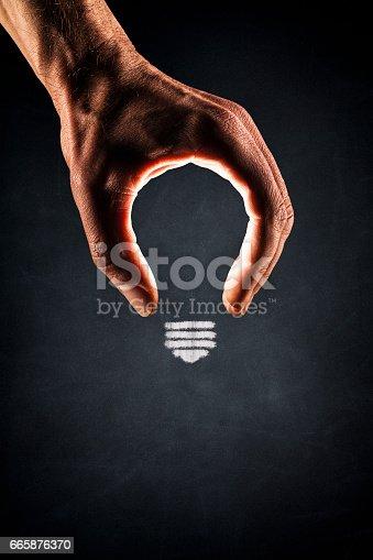 istock Human Hand Light Bulb on Blackboard - New Idea Glowing 665876370