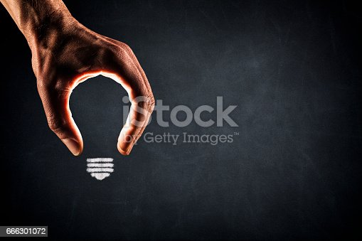 Photography of a hand forming a light bulb on a blackboard.
