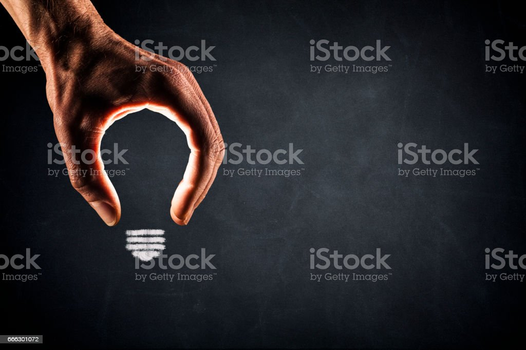 Human Hand Light Bulb on Blackboard - New Idea Glowing stock photo