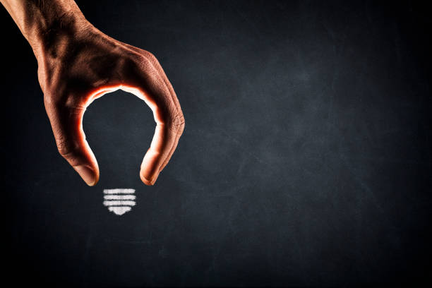 Human Hand Light Bulb on Blackboard - New Idea Glowing - foto stock