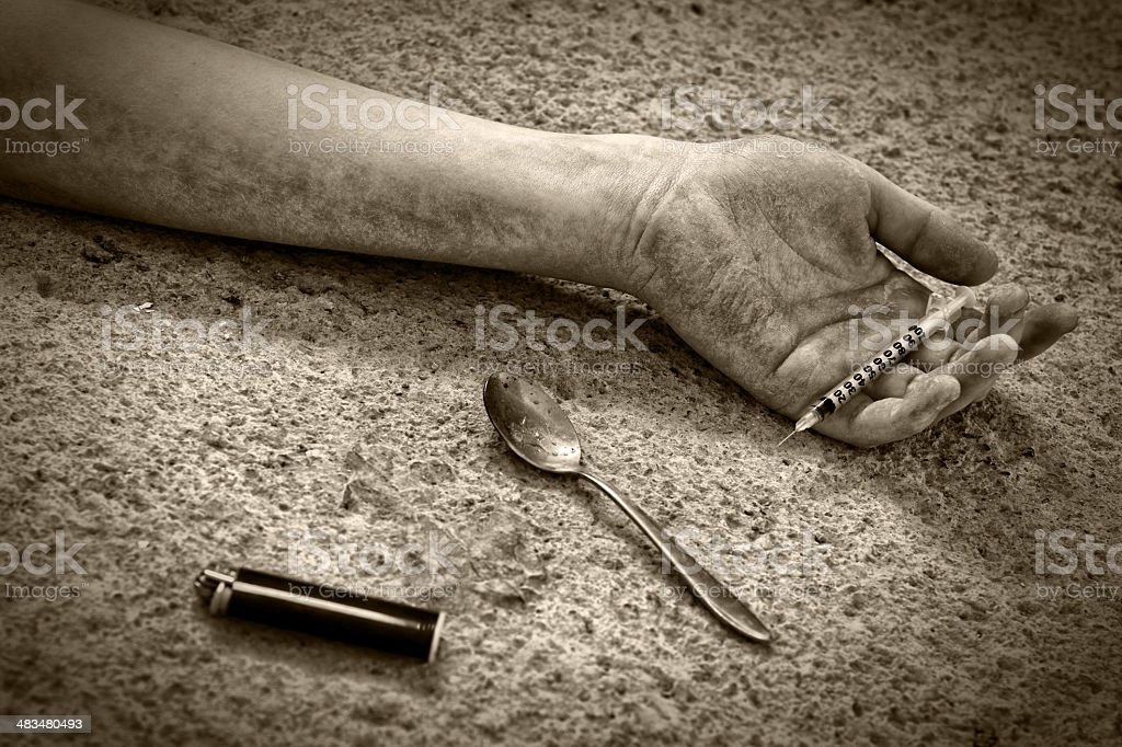 Human hand on the floor with syringe royalty-free stock photo