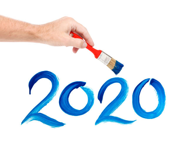 Human hand painting with paintbrush 2020 on window stock photo
