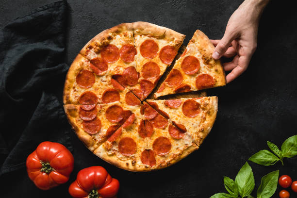 Human hand picking slice of pepperoni pizza Hand picking slice of pepperoni pizza. Pizza party. Hot italian pepperoni pizza on black concrete background, top view pizza stock pictures, royalty-free photos & images