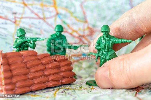 istock Human hand playing war with green plastic soldier with rifle 470630398