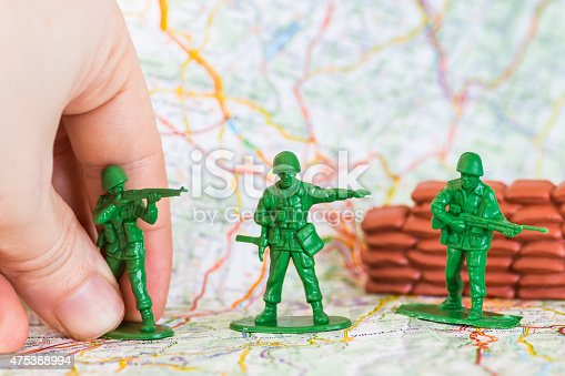 istock Human hand playing war with green plastic soldier with rifle 475388994