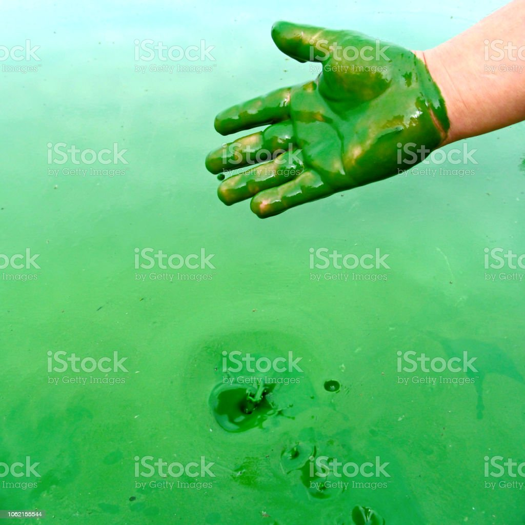 Human hand polluted by green harmful substance and liquid splash. stock photo