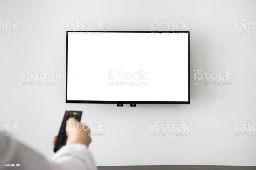 human hand pressing remote control with blank screen television on...