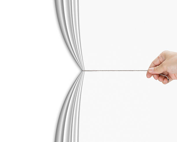 human hand pulling open white blank curtain with empty behind stock photo