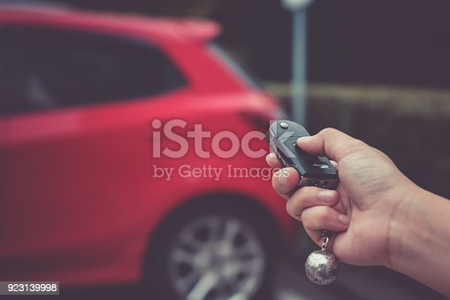 istock Human hand pushing button on remote control car key 923139998