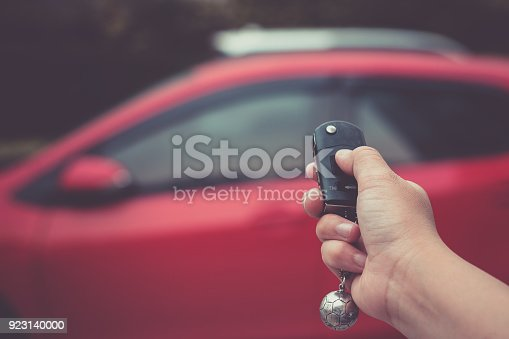 istock Human hand pushing button on remote control car key 923140000