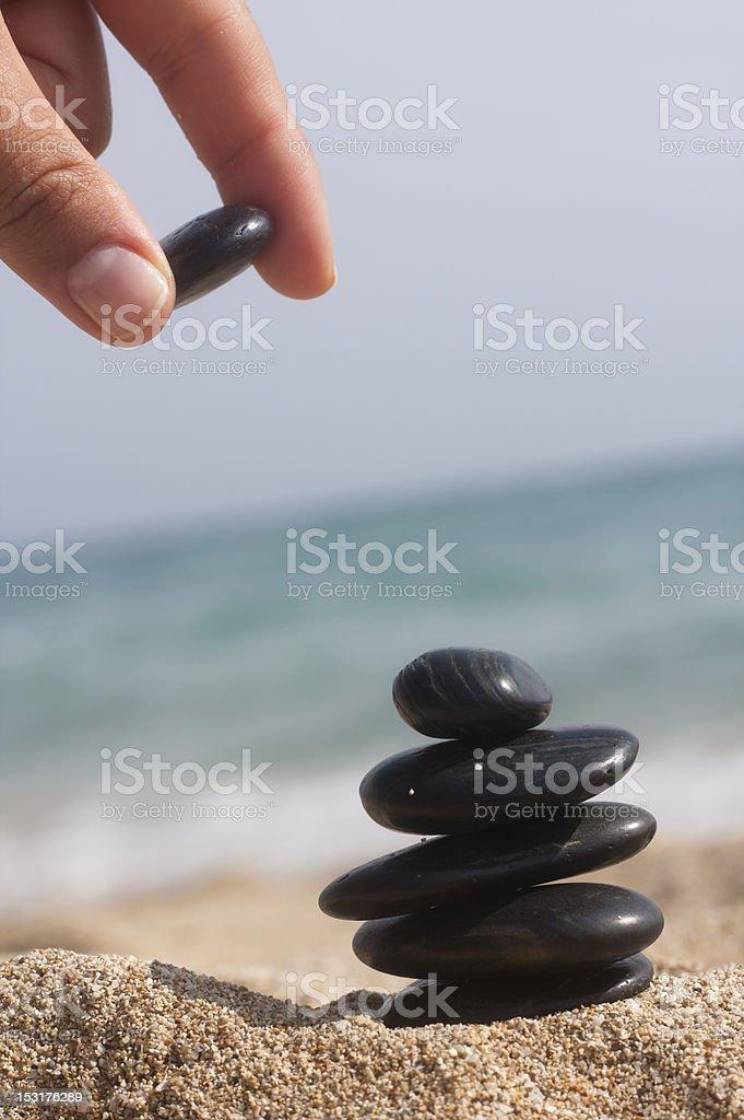 human hand put last stone at the pyramid royalty-free stock photo