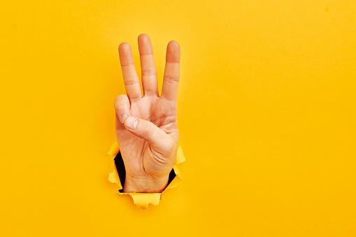 Human hand reaching through torn yellow paper sheet showing number three