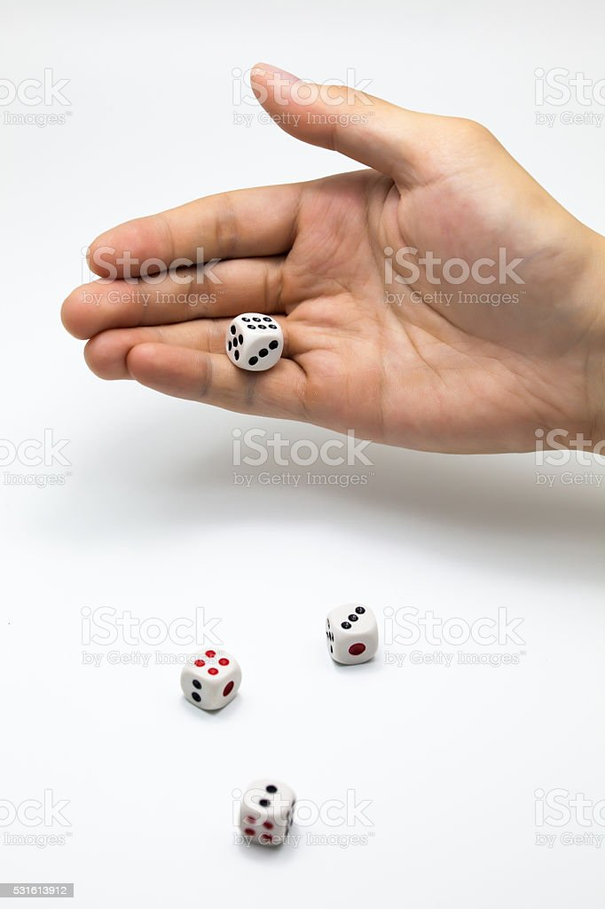 Human hand ready to roll the dice on white isolated stock photo