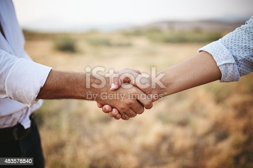 Selective focus farmers business hand shake on field.