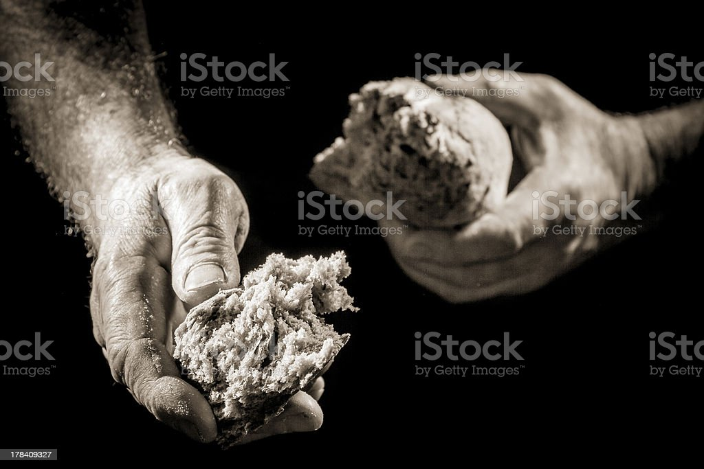 Human hand sharing with bread as charitable action stock photo