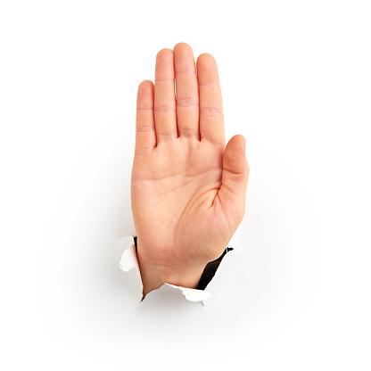 Human hand reaching through torn white paper sheet showing