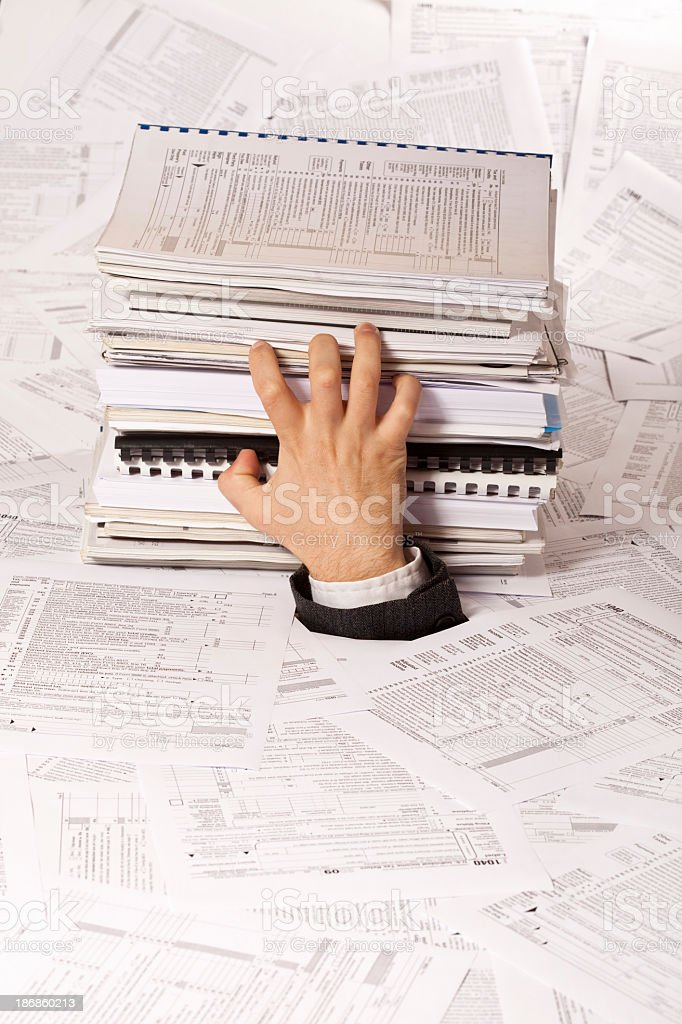 Human hand sinking in paper sheets royalty-free stock photo
