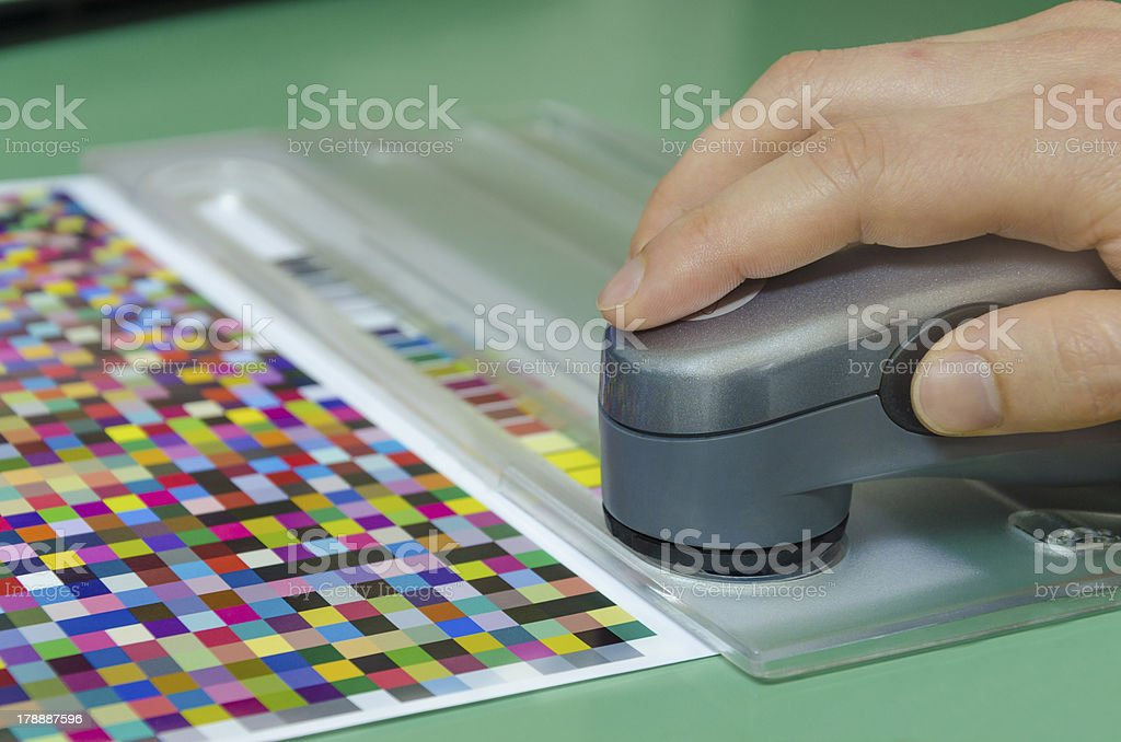 human hand, spectrophotometer measures color patches for profile creation stock photo
