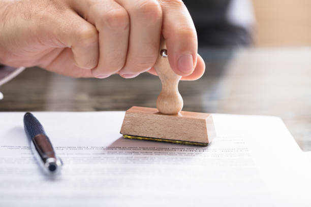 Human Hand Stamping Document Close-up Of A Human Hand Stamping Document On Desk legislation stock pictures, royalty-free photos & images