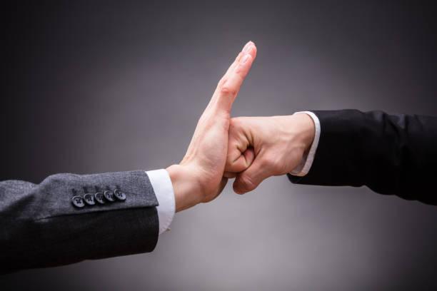 mão humana parando o punho de uma pessoa com raiva - violência - fotografias e filmes do acervo