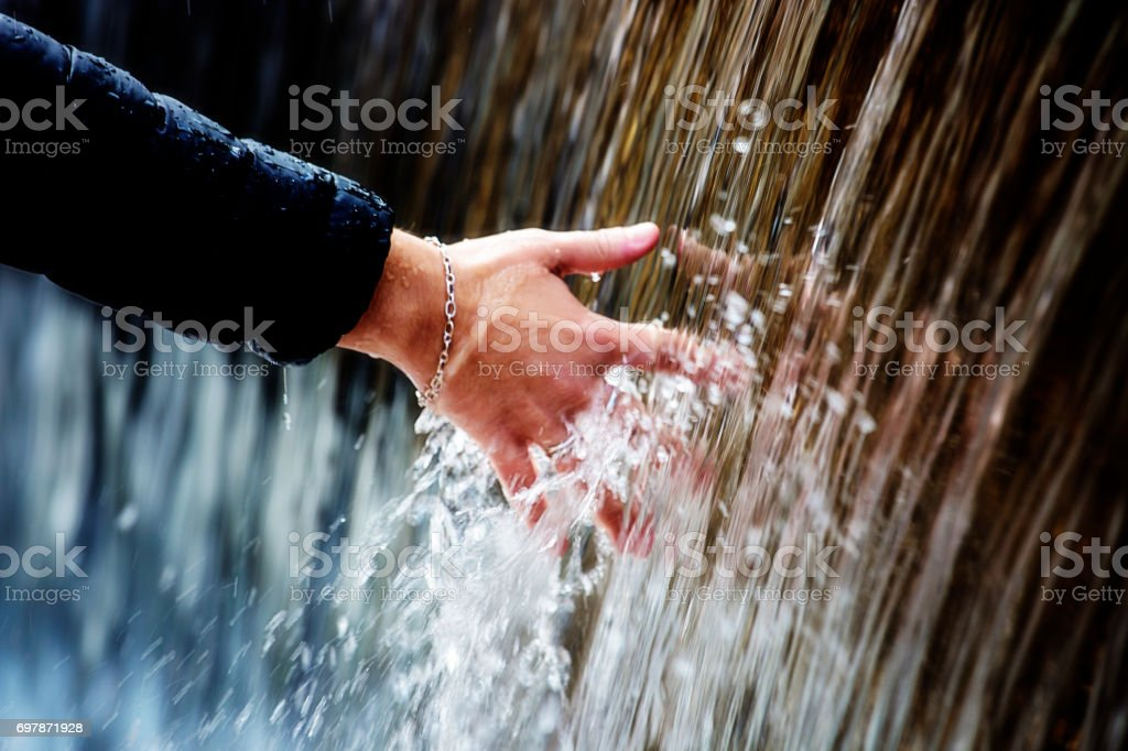 Human hand touches falling water stock photo