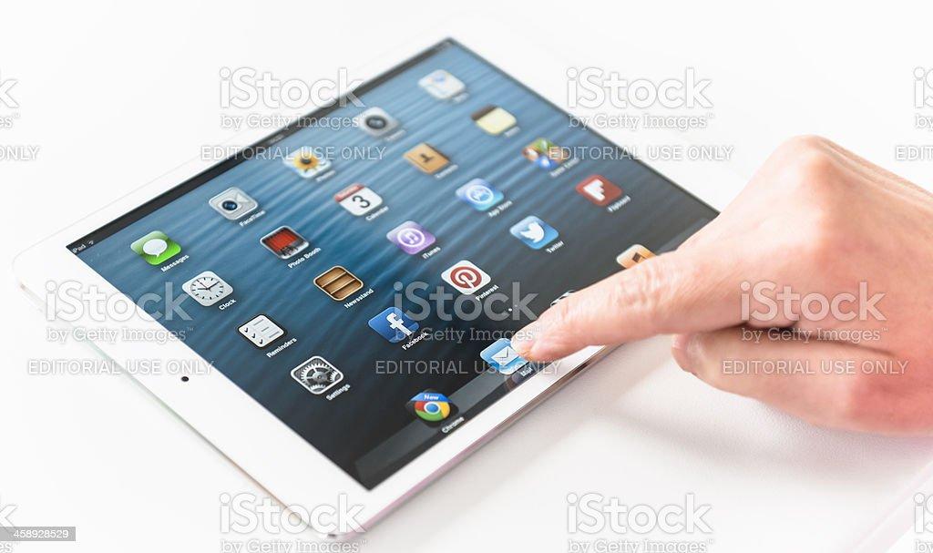 Human hand touching the mail icon on Ipad Mini royalty-free stock photo