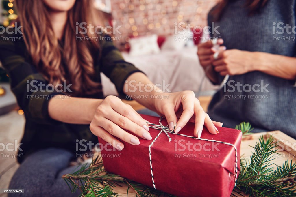 Human hand tying a string on christmas present stock photo