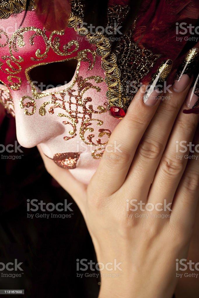Human hand with beautiful manicure holding venetian mask royalty-free stock photo