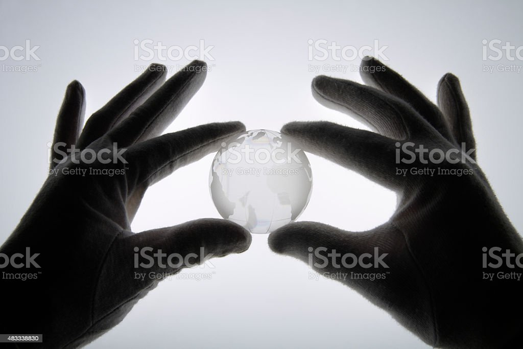 Human hand with cotton gloves holding glass globe against white stock photo