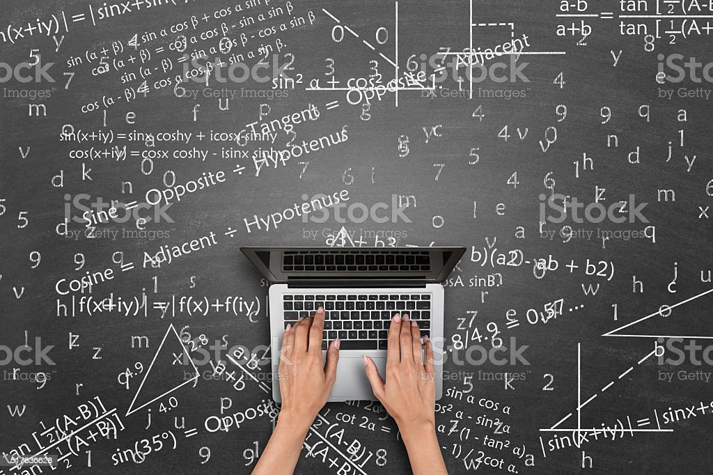 Human hand working on laptop against blackboard with mathematical formulas stock photo