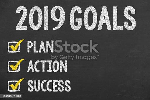 istock Human Hand Writing New Year 2019 Goals on Chalkboard 1083507130