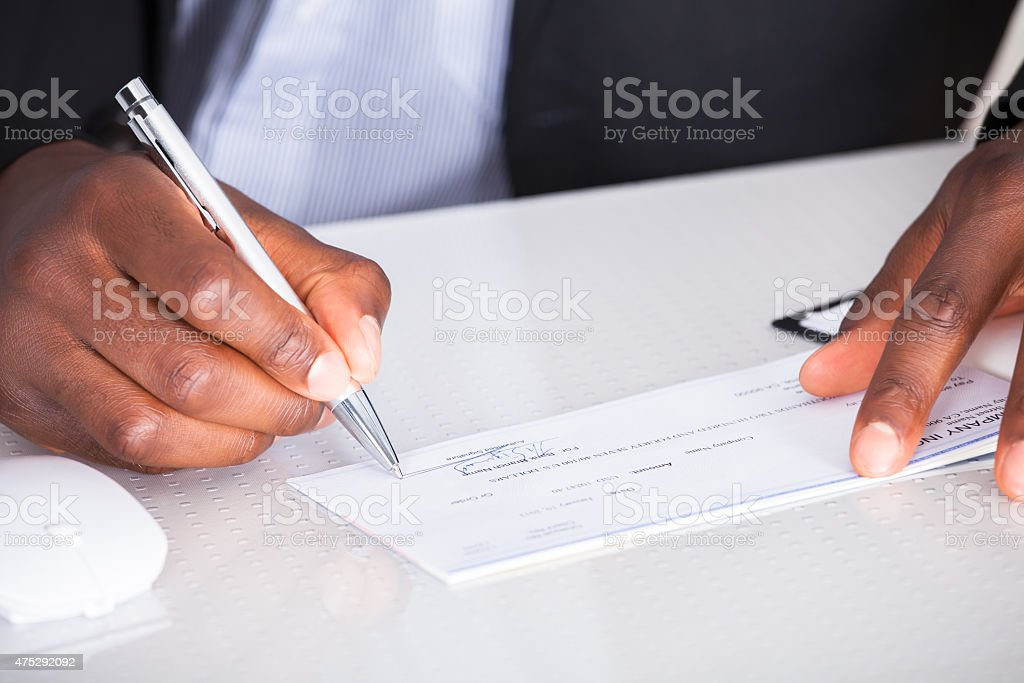 Human Hand Writing On Cheque stock photo