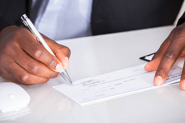 human hand writing on cheque - blank check stock photos and pictures