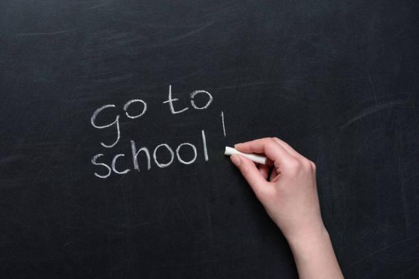 menschliche hand schreiben satz gehen zur schule mit kreide tafel - kreidetafel zitate stock-fotos und bilder