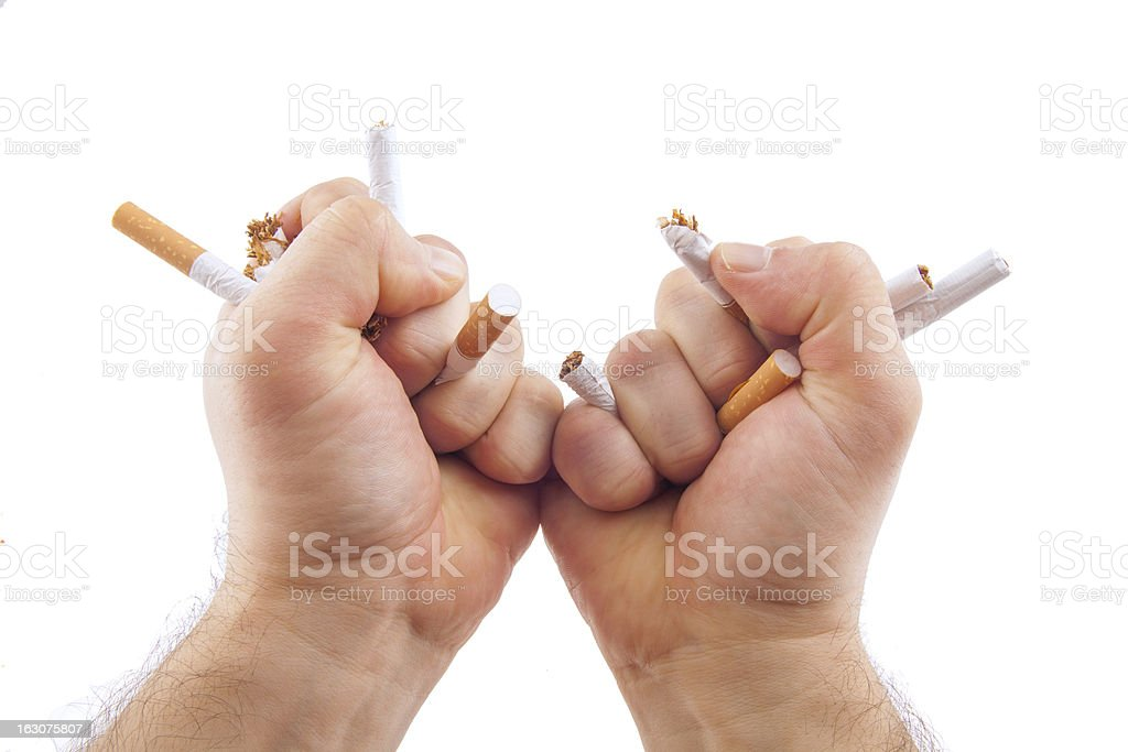 Human hands breaking cigarettes stock photo