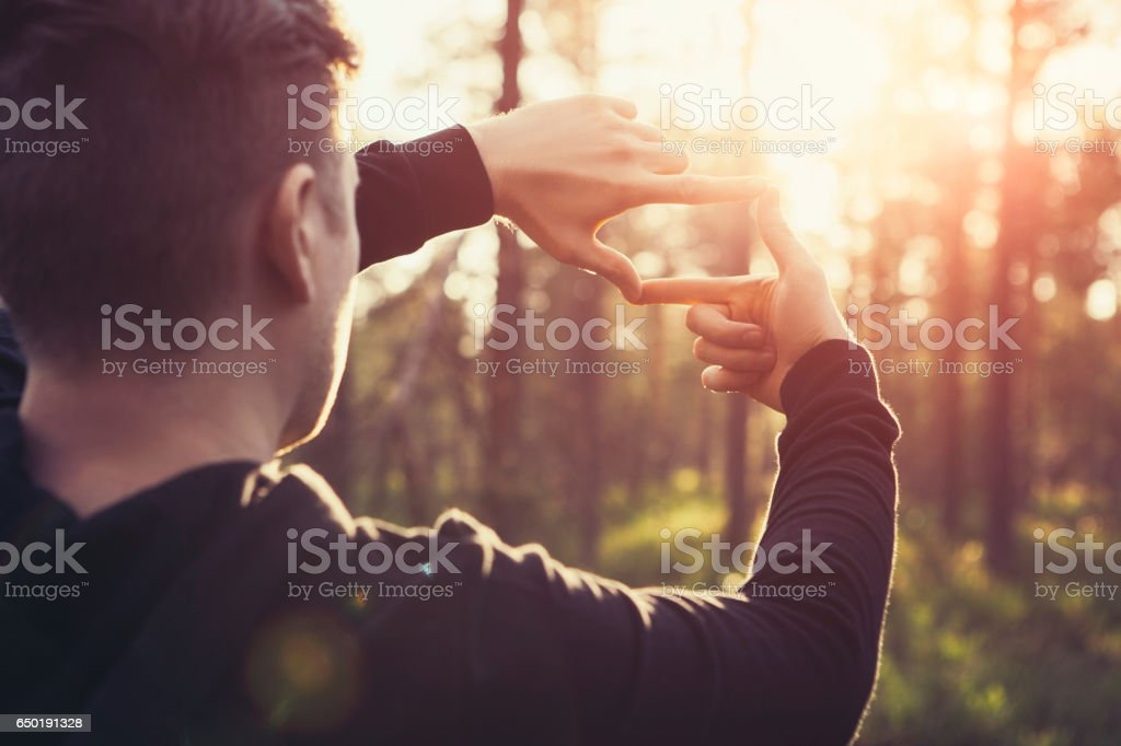 Human hands framing distant sun rays – zdjęcie