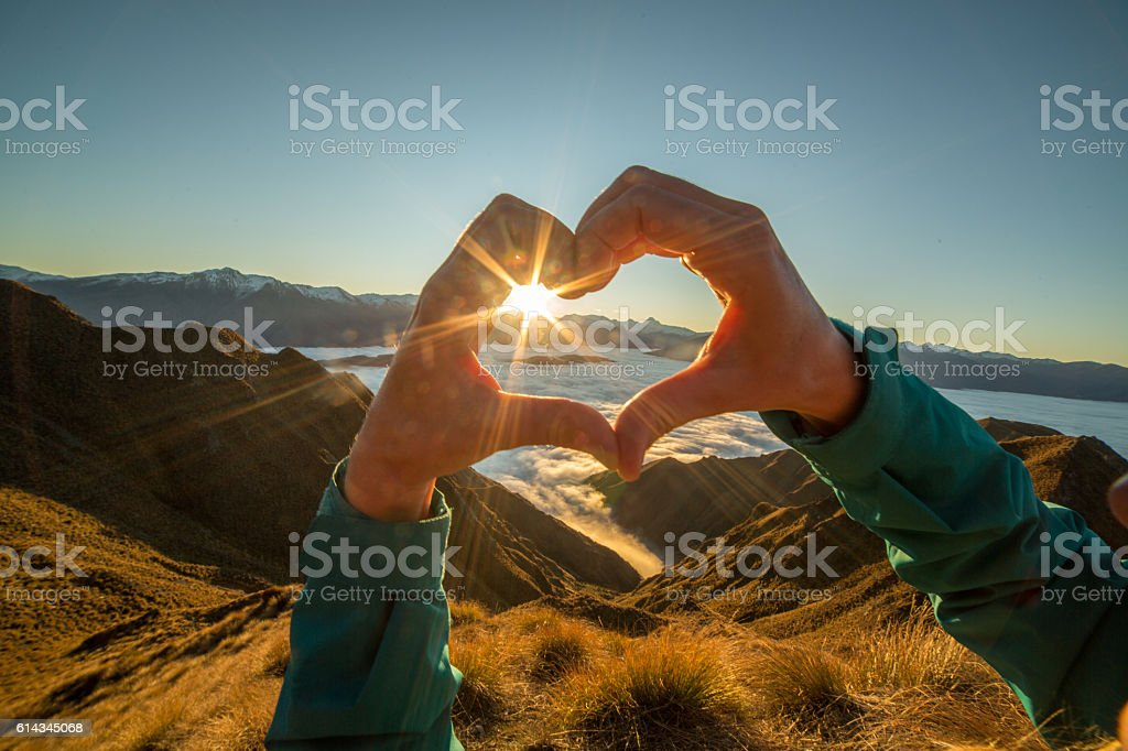 Close up of woman\'s hands making a heart shape finger frame to the...