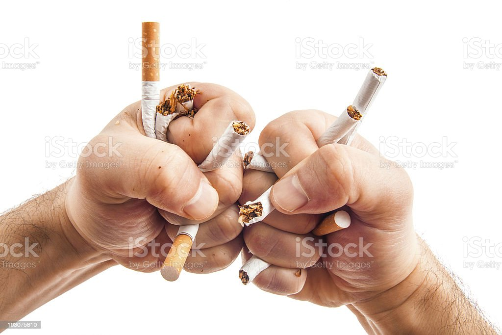 Human hands heatedly breaking cigarettes stock photo