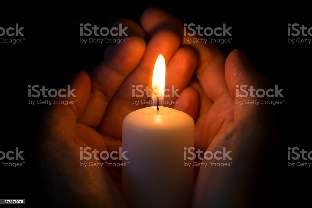 Human hands holding a burning candle stock photo