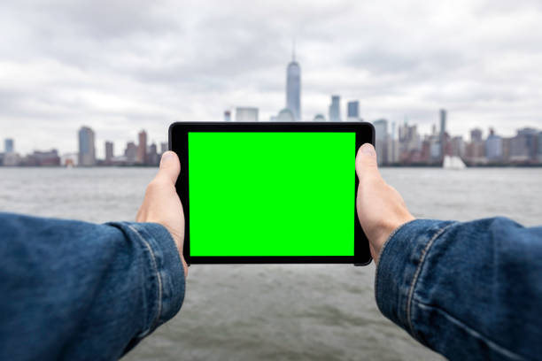 human hands holding a digital tablet with new york city lower manhattan in the background - green screen background stock photos and pictures