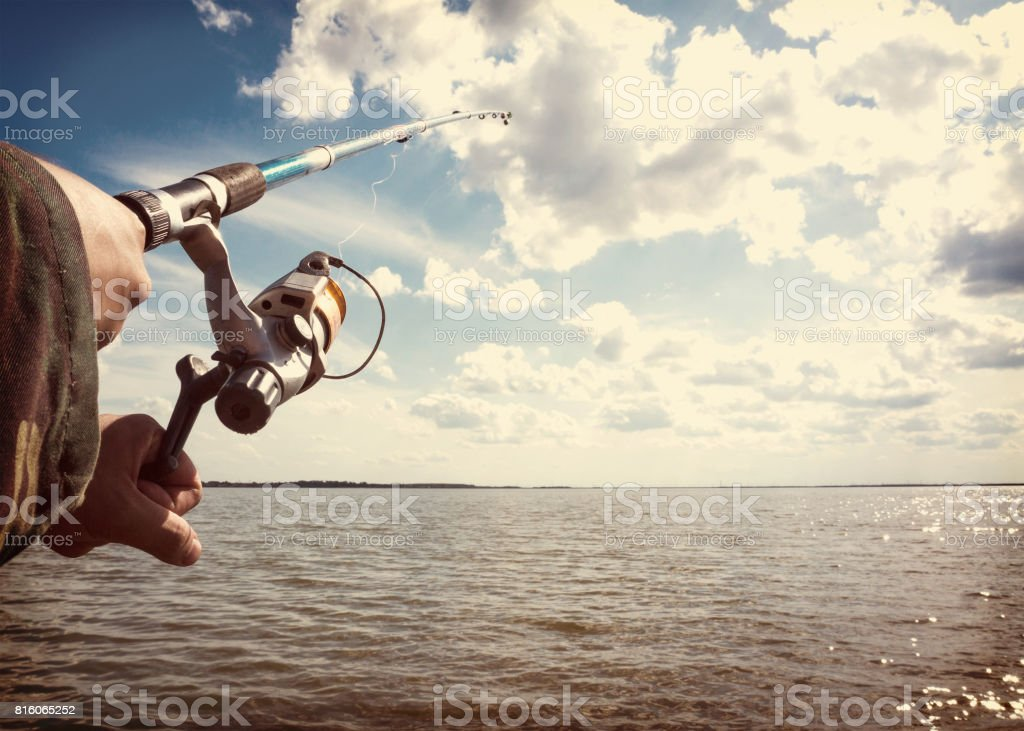 human hands holding a fishing-rod stock photo