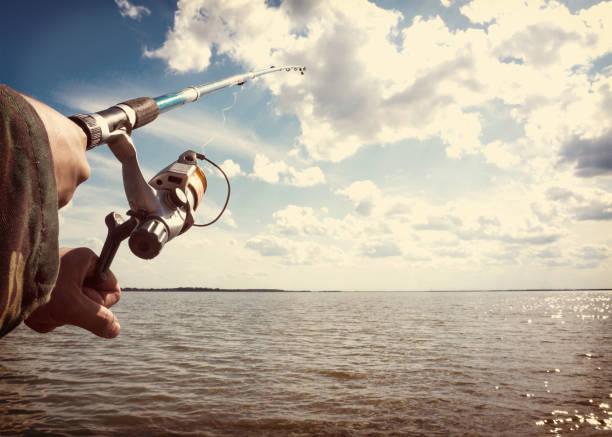 mains humaines, tenant une canne à pêche - technique photographique photos et images de collection