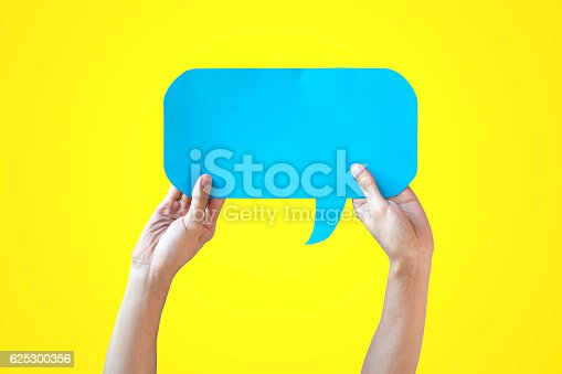 istock Human Hands Holding Blue Speech Bubble Over Yellow Background 625300356