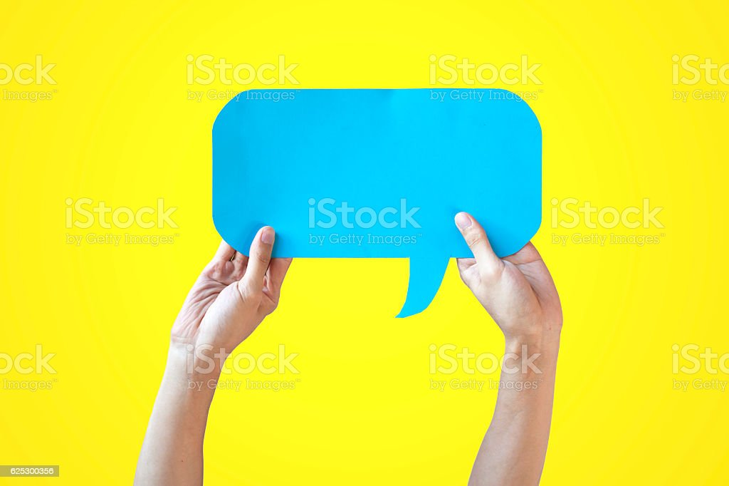 Human Hands Holding Blue Speech Bubble Over Yellow Background – Foto